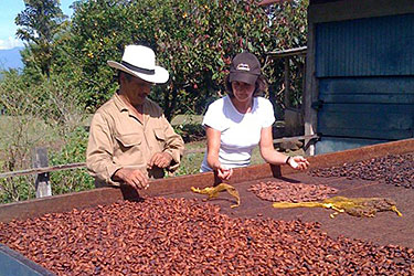 Gail and a cacao farmer drying beans