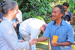 Gail shakes hands with a cacao farmer
